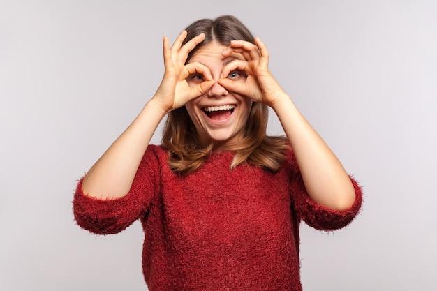 Portret beztroskiej szczęśliwej dziewczyny patrzącej przez otwory na palce, gest ręki lornetki
