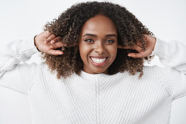 Portret beztroskiej szczęśliwej i radosnej charyzmatycznej afroamerykańskiej kobiety śmiejącej się i uśmiechającej szczęśliwie blisko uszu palcami wskazującymi i wpatrującej się zachwyconej z przodu