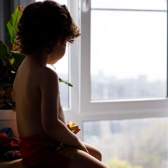 Portret białego dziecka rasy kaukaskiej chłopiec w domu patrząc z okna na zewnątrz. widok z tyłu. dziecko czeka na kogoś