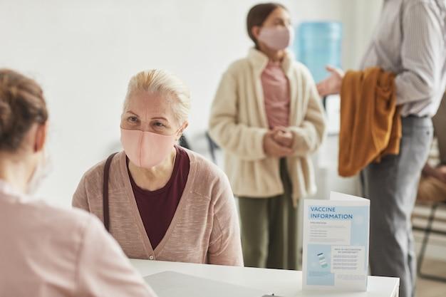 Portret białowłosej starszej kobiety noszącej maskę podczas rejestracji na szczepionkę przeciw covid w centrum medycznym, skopiuj przestrzeń