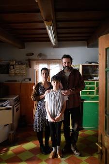 Portret biednej dojrzała para z małą córką w pomieszczeniu w kuchni w domu, pojęcie ubóstwa.