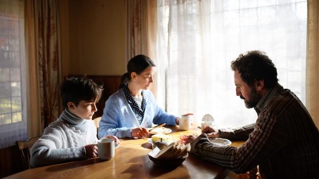Portret biednej smutnej małej dziewczynki z rodzicami, jedzenie w domu w domu, pojęcie ubóstwa.