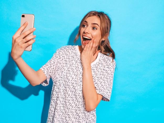 Portret bierze fotografii selfie rozochocona młoda kobieta. piękna dziewczyna trzyma aparat smartphone. uśmiechnięty model pozuje blisko błękit ściany w studiu. zaskoczony model zaskoczony