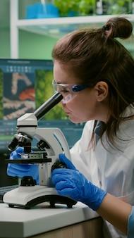 Portret biologa w białym fartuchu, pracującego w laboratorium eksperckim, patrzącego w mikroskop analizujący organiczny liść gmo