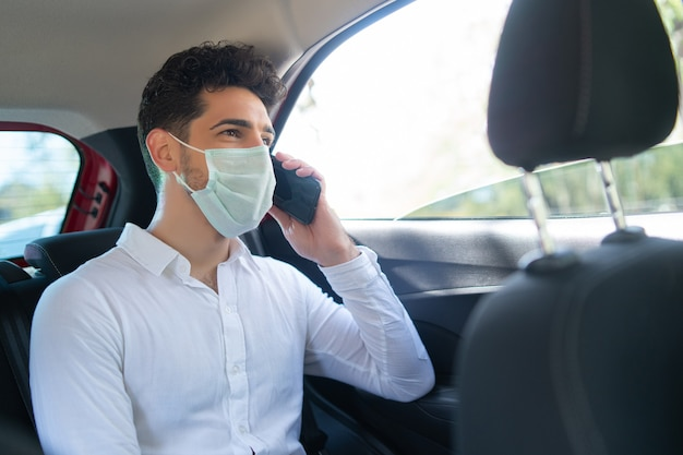Portret biznesmen noszenie maski i rozmawia przez telefon w drodze do pracy w samochodzie. pomysł na biznes. nowa koncepcja normalnego stylu życia.