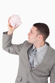Portret biznesmen patrzeje w prosiątko banku