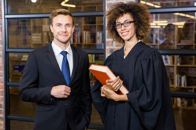 Portret biznesmen pozycja z prawnikiem blisko biblioteki w biurze