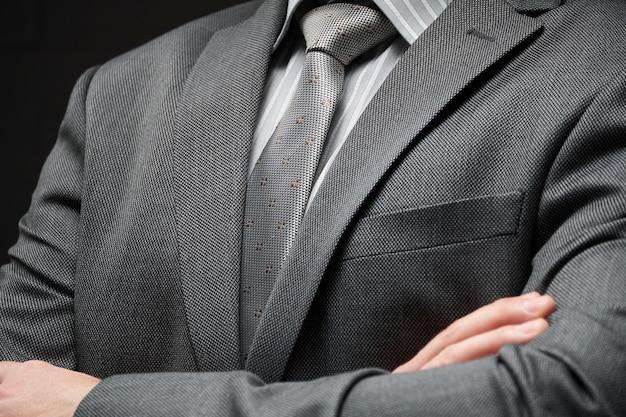 Portret biznesmen ubrany w szary garnitur, ciemne tło ściany