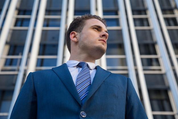 Portret biznesmen w garniturze pozuje pewnie.