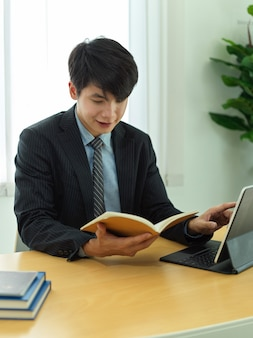 Portret biznesmena czytania informacji w jego książce harmonogramu podczas pracy z cyfrowym tabletem