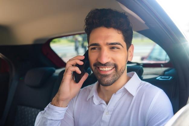 Portret biznesmena rozmawiającego przez telefon w drodze do pracy w samochodzie