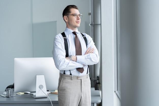 Portret biznesmena stoi przy oknie w biurze.