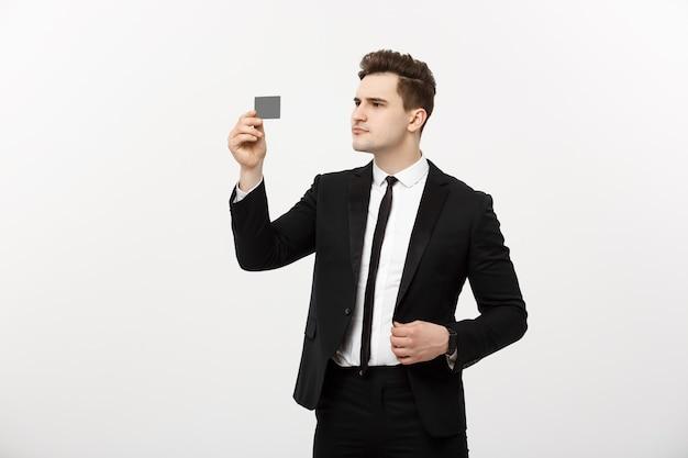 Portret biznesmena trzymającego kartę kredytową i poważnie sprawdzającego na białym tle nad szarym tłem.