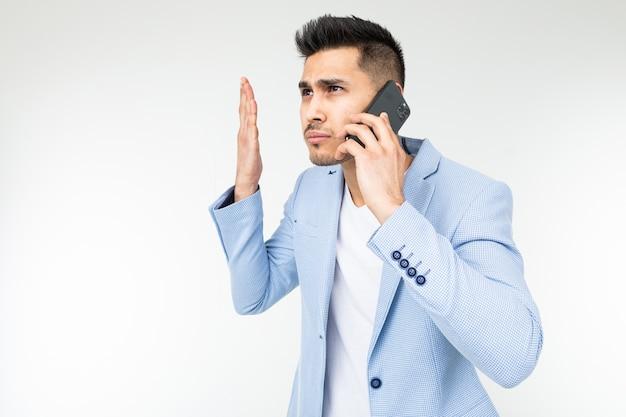 Portret biznesmena w niebieskiej kurtce rozmawia przez telefon z niezadowoleniem w ważnych sprawach.