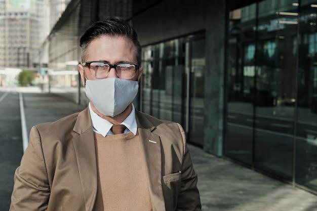 Portret biznesmena w okularach i masce ochronnej patrząc na kamery, stojąc w mieście