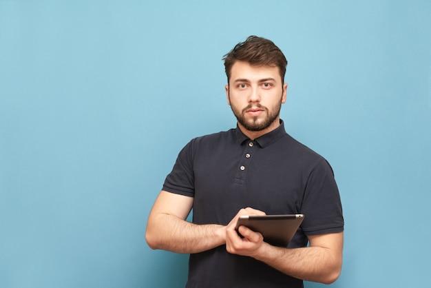 Portret biznesmena z brodą, stojącego na niebiesko z tabletem w rękach, na sobie t-shirt