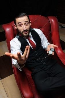 Portret biznesmena z zegarem siedzi na krześle młody człowiek zabawny z zegarem, siadając.