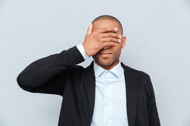Portret biznesmena zakrywającego oczy na białym tle