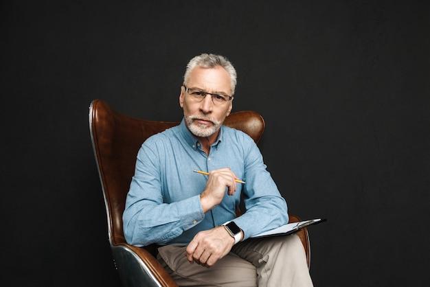 Portret biznesowego mężczyzny w średnim wieku 50 lat z siwymi włosami i brodą pracującego z dokumentami, siedząc na drewnianym fotelu w biurze, odizolowany na czarnej ścianie