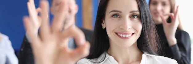 Portret bizneswoman demonstruje ok gest na tle współpracowników biznesowych