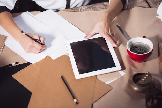 Portret bizneswoman, która pracuje w biurze i sprawdza szczegóły nadchodzącego spotkania w swoim notatniku oraz pracuje w studio na poddaszu.