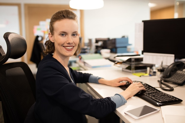 Portret bizneswoman pisania na klawiaturze w biurze
