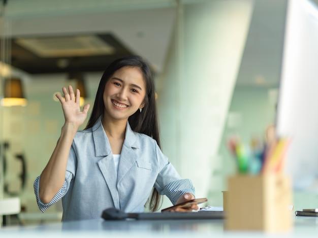 Portret bizneswoman pokazuje pięć palców, macha ręką, aby się przywitać, cześć lub do widzenia