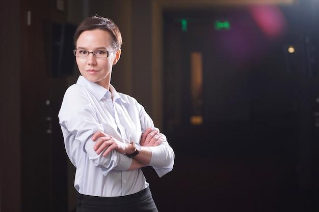Portret bizneswoman pozycja przed okno w budynku biurowym.