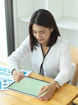 Portret bizneswoman pracuje z makiety tabletu i dokumentacji na drewnianym stole