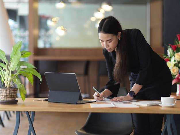 Portret bizneswoman pracuje z papierkową robotą, stojąc w miejscu pracy