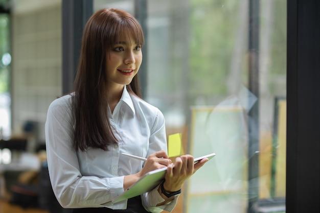 Portret bizneswoman robi notatkę na tablecie z rysikiem podczas stania