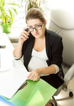 Portret bizneswoman siedzącej na krześle i pracująca z papierami