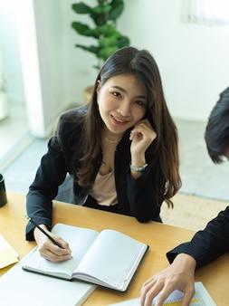Portret bizneswoman uśmiecha się podczas konsultacji na temat jej pracy ze współpracownikiem w biurze