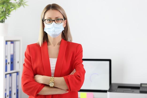 Portret bizneswoman w medycznej masce ochronnej i kolorze w biurze