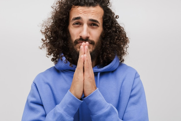 Portret błagającego nieogolonego mężczyzny w casualowej bluzie modlącego się z dłońmi razem na białym tle