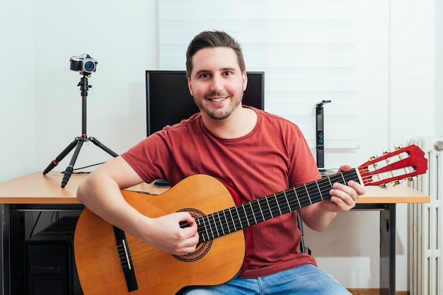 Portret blogera grającego na gitarze z domowego studia nagrań.