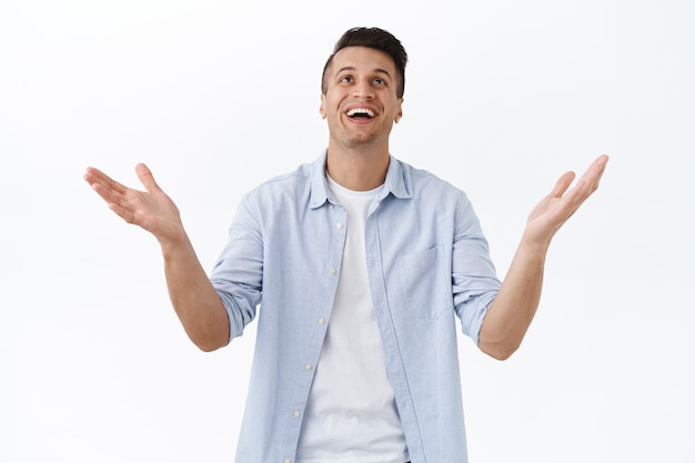 Portret błogosławionego szczęśliwego przystojnego mężczyzny dziękującego bogu z ulgą, podnoszącego ręce i szeroko uśmiechającego się, wdzięcznego za cud, spełnienie marzeń lub życzeń, stojący wesoło na białej ścianie