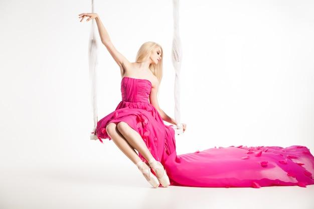 Portret blond baleriny w baletkach i pięknej różowej sukience z latającą spódnicą na huśtawce