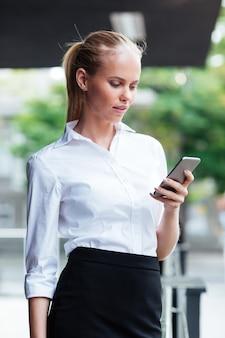 Portret blond bizneswoman wiadomości sms stojącej na zewnątrz