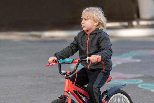 Portret blond chłopca na rowerze.