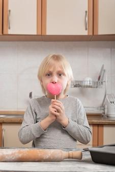 Portret blond chłopca w kuchni z różowym lizakiem w jego rękach