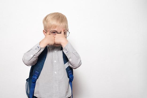 Portret blond chłopca w okularach iz plecakiem szkolnym pokazuje klasę gestów. koncepcja szkoły