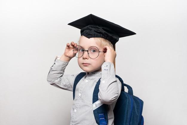 Portret blond chłopiec w akademickim kapeluszu i tornister. koryguje okulary. białe tło. koncepcja szkoły