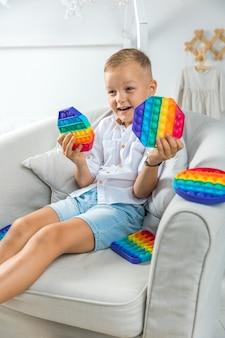 Portret blond chłopiec z pop to sensoryczna zabawka różne formy