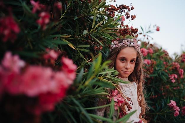 Portret blond dziewczyna z kręconymi włosami ubrana w sukienkę komunijną na tle kwiatów