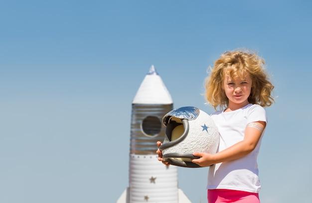 Portret blond dziewczynka w stroju astronauty z rakietą marzy o zostaniu kosmonautą.