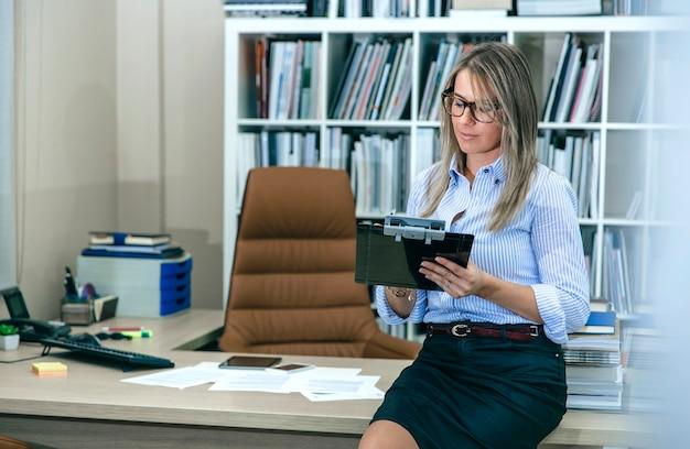 Portret blond kobieta pisze notatki, siedząc nad jej stołem na pulpicie