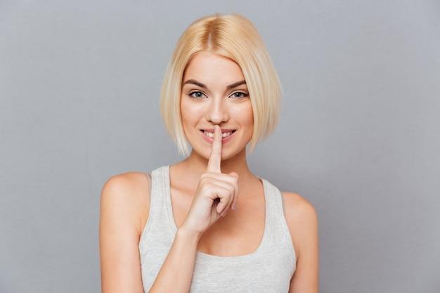 Portret blond kobiety wykonującej gest ciszy