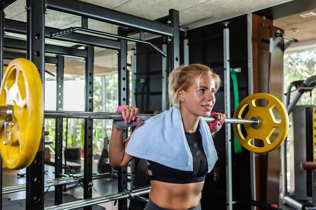 Portret blond kobiety wykonującej prasę na ramię z ciężką sztangą podczas treningu w nowoczesnej siłowni
