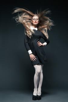 Portret blond młoda piękna pozowanie kobieta nosi okulary i czarną sukienkę z białym kołnierzykiem. jej długie falujące włosy.